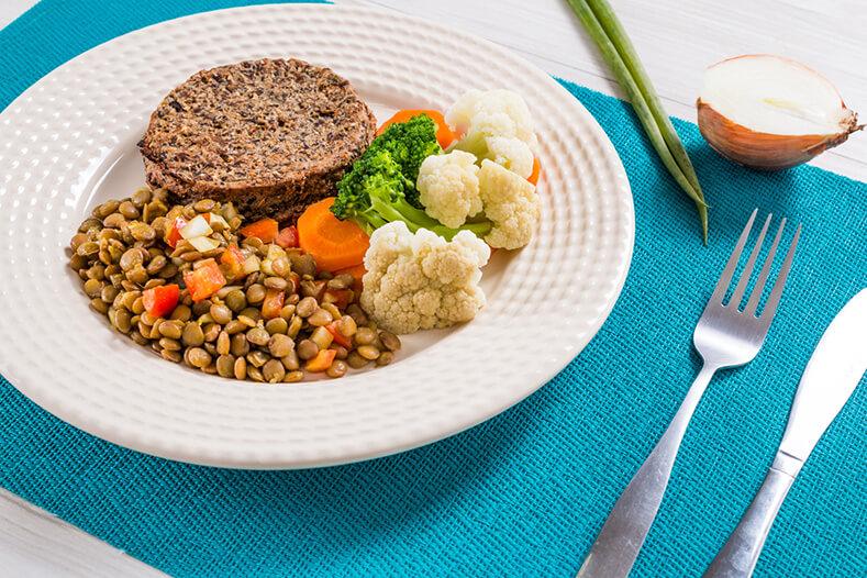 prato contendo hambúrger de faláfel, lentilha, e mix de legumes com um talher ao lado