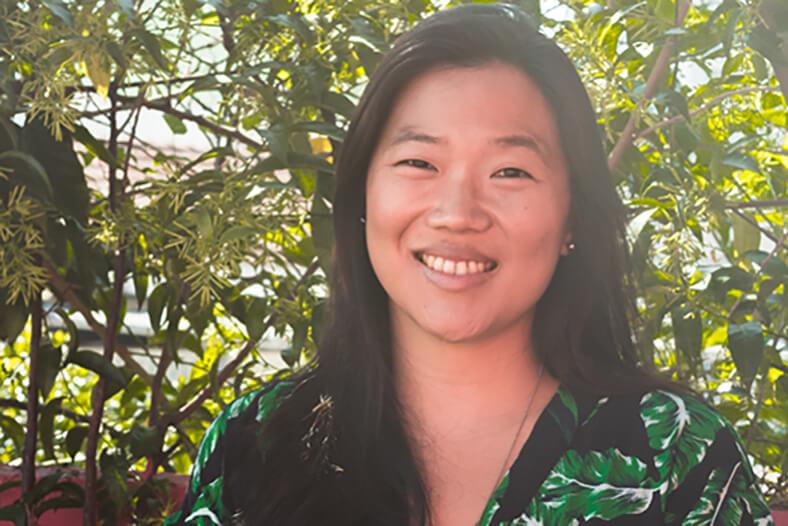 Viviane Kim - mulher japonesa com arbusto ao fundo