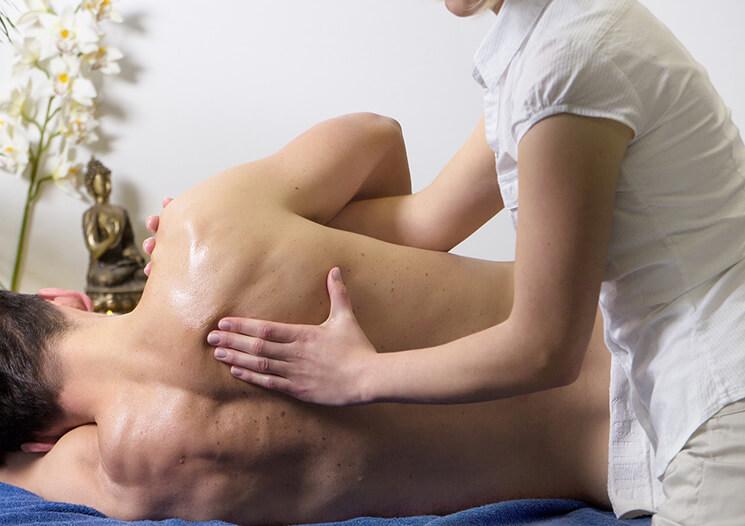 homem deitado de costas com uma mulher fazendo massagem nas costas dele
