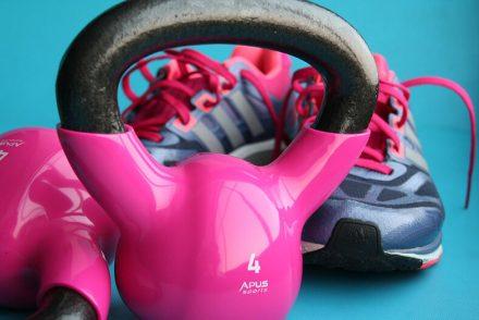 dois pesos rosas de academia com um par de tenis ao fundo