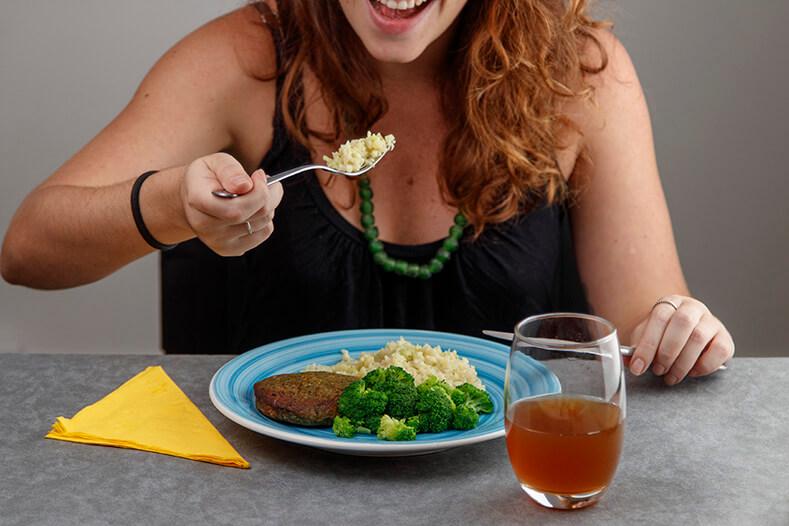 mulher comendo com um garfo indo em direção a boca